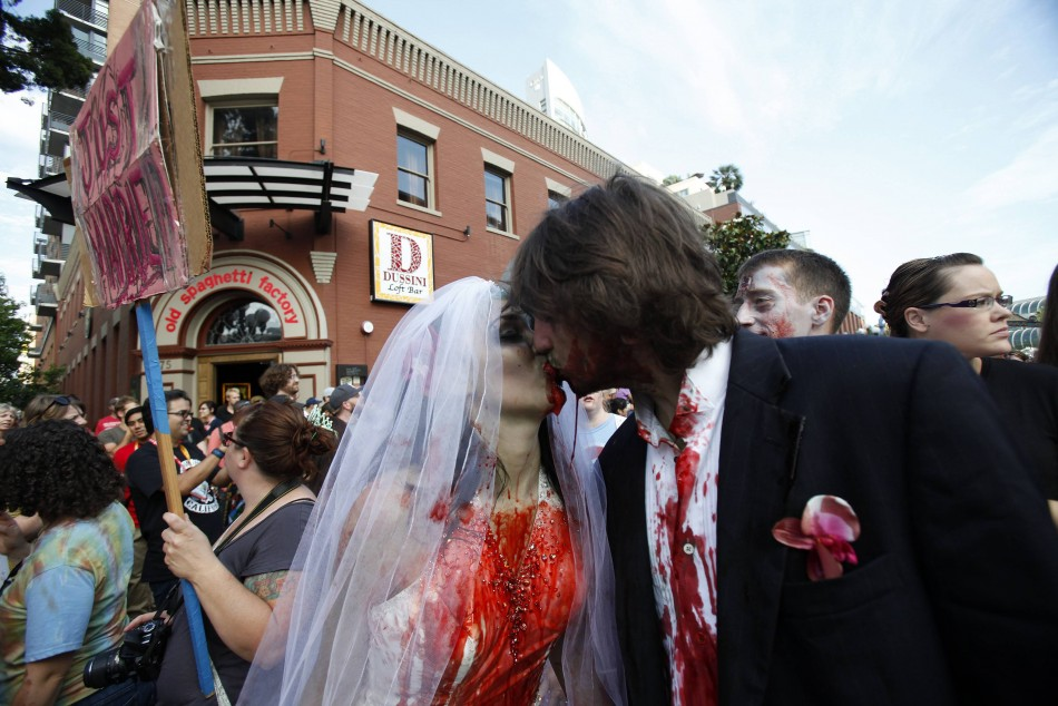 A couple dressed up as zombies kisses during a zombie walk during the Comic Con International convention in San Diego