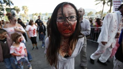A woman dressed up as a zombie takes part in a zombie walk during the Comic Con International convention in San Diego