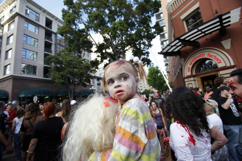 A young girl dressed up as a zombie takes part in a zombie walk during the Comic Con International convention in San Diego