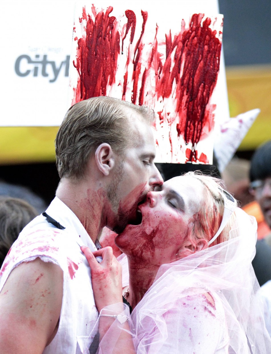 A couple dressed up as zombies takes part in a zombie walk during Comic Con International convention in San Diego