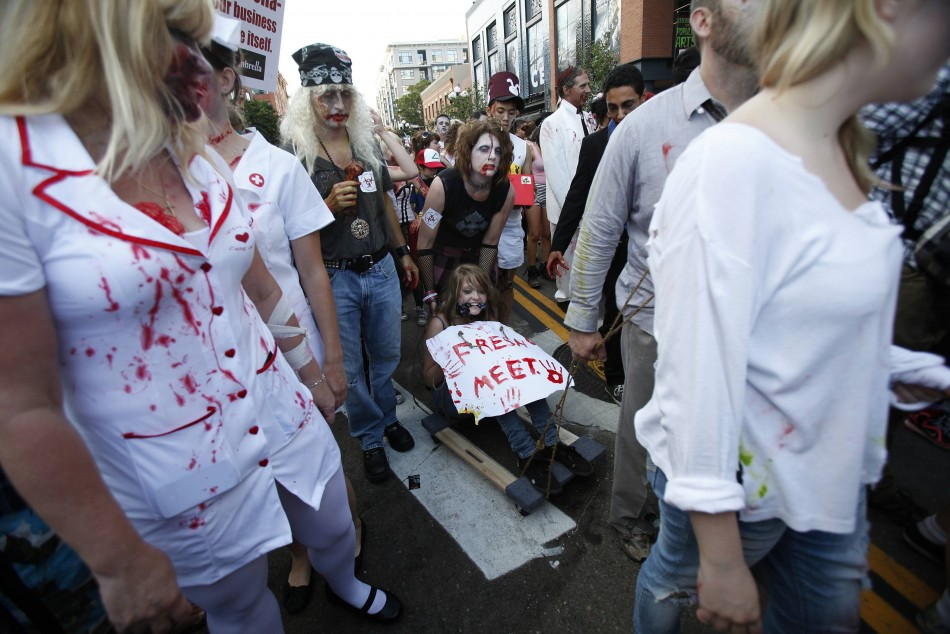 People dressed up as zombies take part in a zombie walk during the Comic Con International convention in San Diego