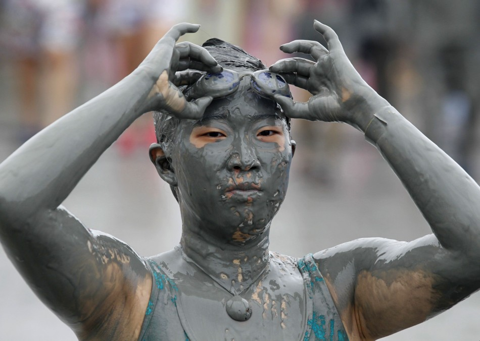 A woman takes off her goggles at the Boryeong Mud Festival on Daecheon beach in Boryeong