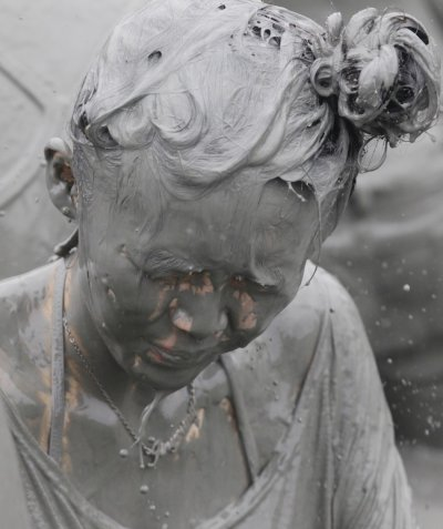 A woman plays in mud during the Boryeong Mud Festival at Daecheon beach in Boryeong