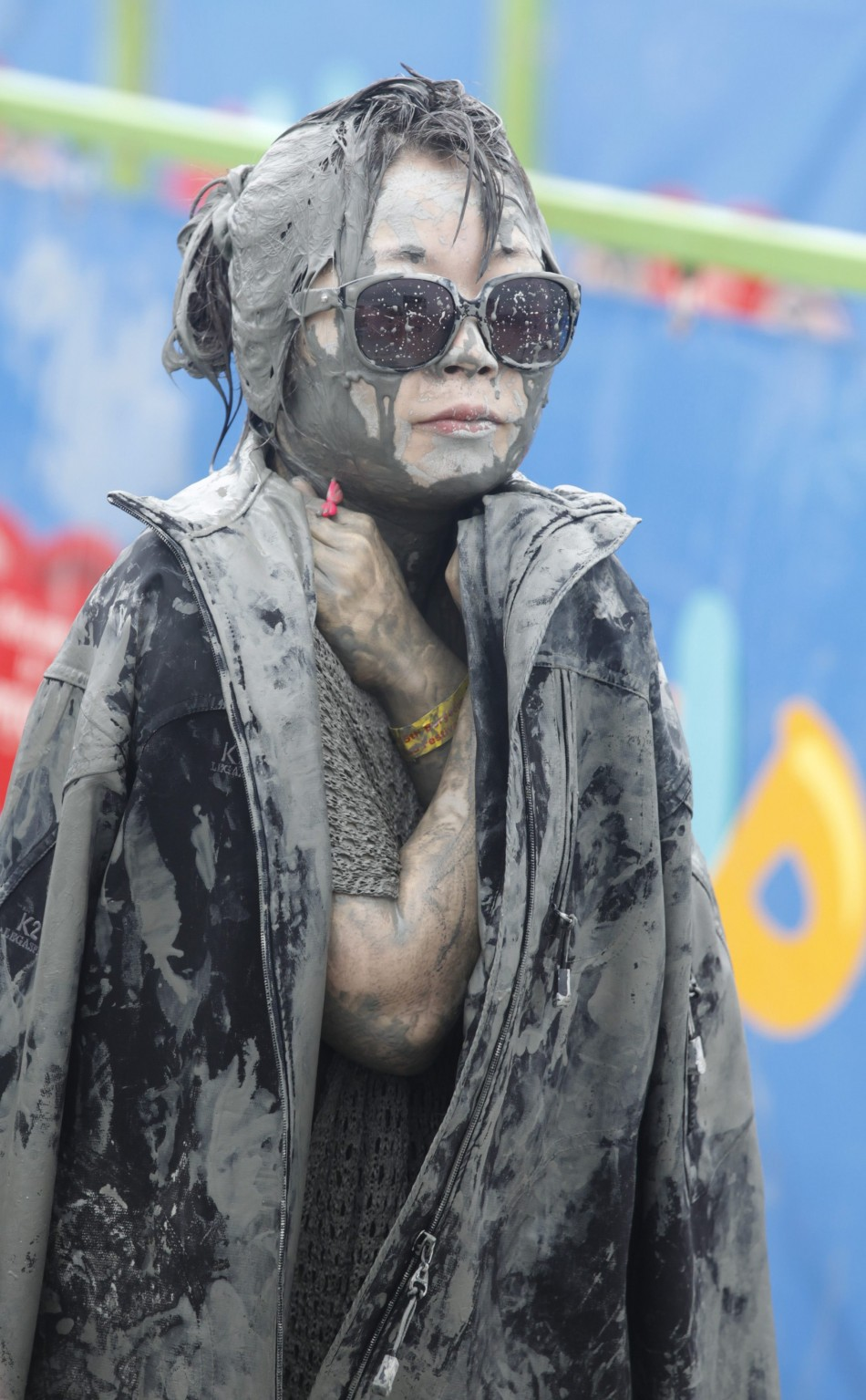 A woman wears a jacket to warm herself during the Boryeong Mud Festival at Daecheon beach in Boryeong