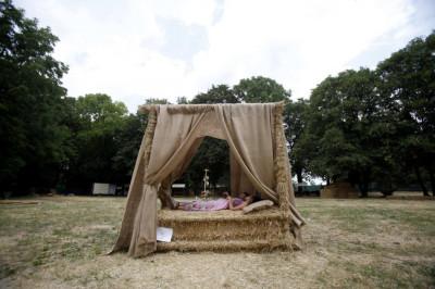 Girls rest on a straw art installation during the 7th Straw - Land Art Festival in Osijek
