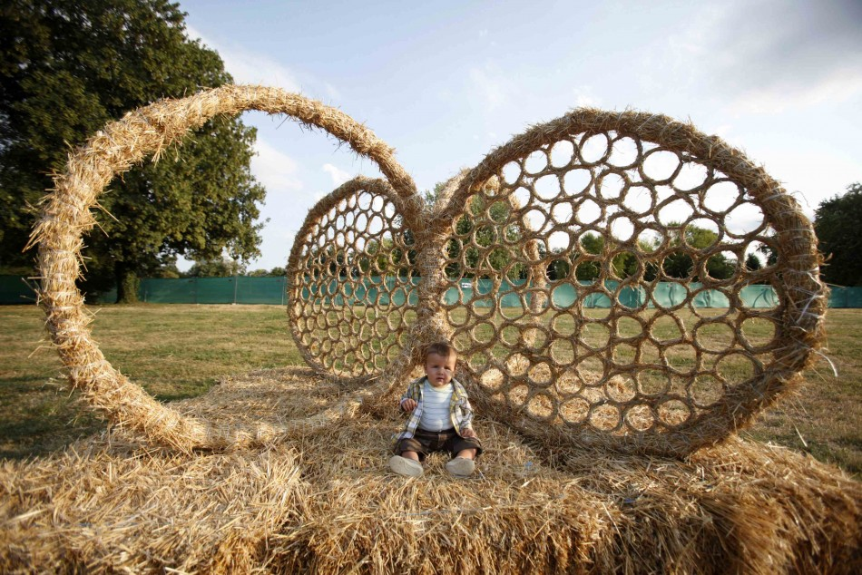 A child sits in a straw art installation during the 7th Straw - Land Art Festival in Osijek