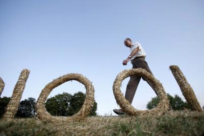 A man walks past a straw art installation during the 7th Straw - Land Art Festival in Osijek