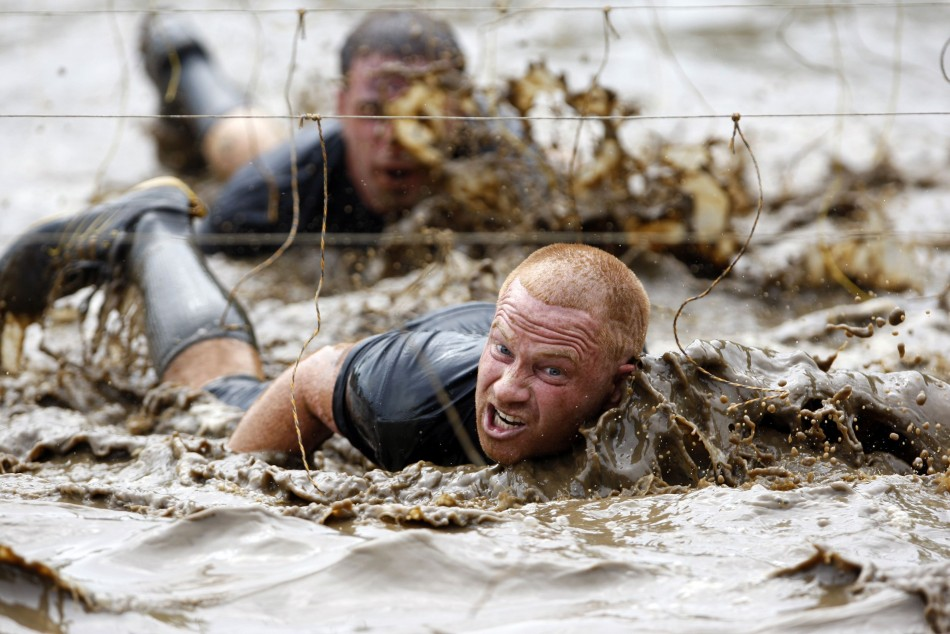 Competitors swim through mud underneath electrified wires during the Tough Mudder at Mt. Snow in West Dover