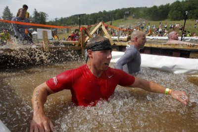 Competitors jump into a vat of ice water during the Tough Mudder at Mt. Snow in West Dover