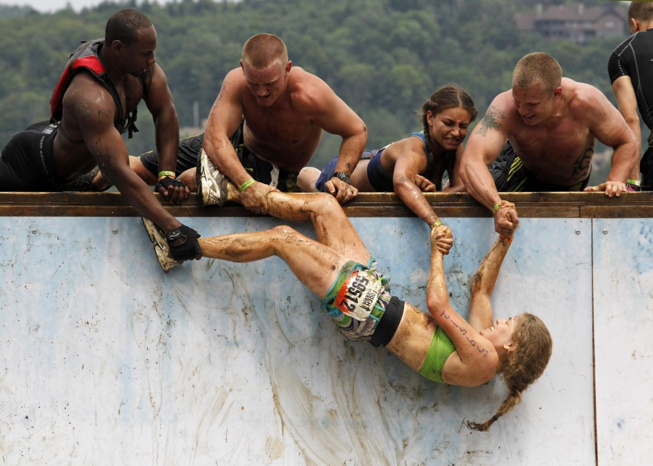 Competitors work to pull a woman up an obstacle where competitors must jump to the top of a half pipe during the Tough Mudder at Mt. Snow in West Dover