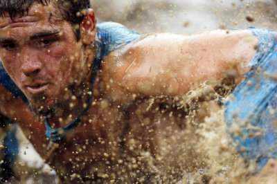 Mud flies in front of a competitor as he swims through mud underneath electrified wires during the Tough Mudder at Mt. Snow in West Dover