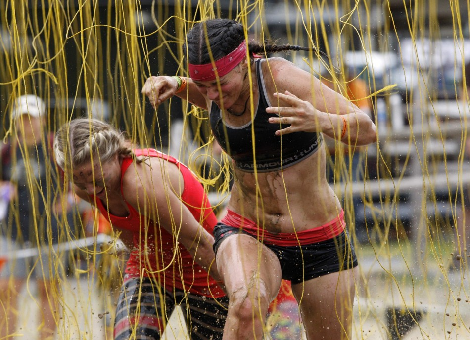 Competitors react as they run through electrified wires before crossing the finish line of the Tough Mudder at Mt. Snow in West Dover