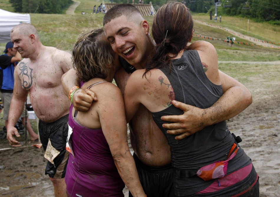 Competitors embrace after crossing the finish line in the Tough Mudder at Mt. Snow in West Dover
