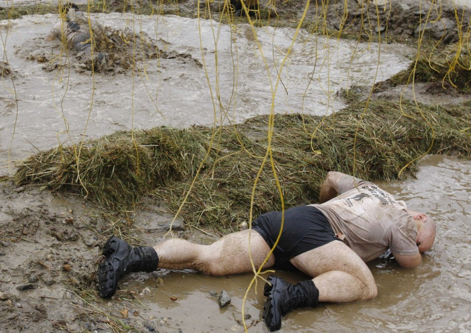 A competitor reacts after being zapped by an electrified wire during the Tough Mudder at Mt. Snow in West Dover