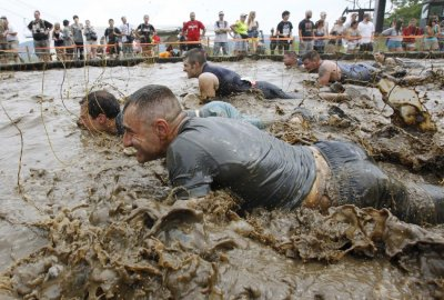 Competitors crawl through mud underneath electrified wires during the Tough Mudder at Mt. Snow in West Dover