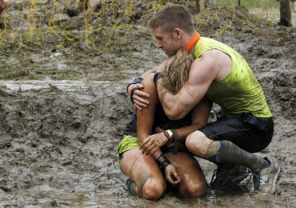 A competitor comforts his teammate after she made it through the last obstacle during the Tough Mudder at Mt. Snow in West Dover