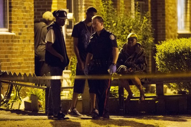 Police survey a crime scene following a shooting in Scarborough, a suburb in east Toronto