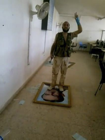 Rebel standing on photo of president on Iraq border
