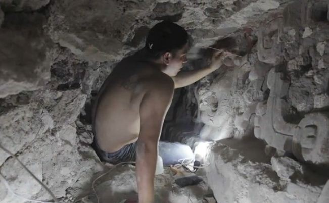 An archaeologist cleans the stucco that depicts several phases of sun at the ancient Mayan temple site in Guatemala. (Photo: Video Screenshot, Brown University)