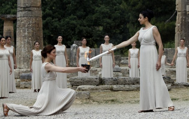 Menegaki (R), playing the role of High Priestess, lights the Olympic flame during the torch lighting ceremony of the London 2012 Olympic Games at the site of ancient Olympia in Greece May 10, 2012. (Photo: Reuters)