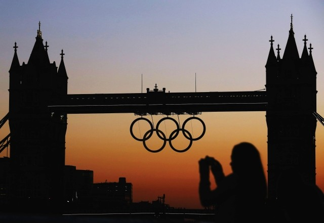A woman photographs the Olympic rings positioned on Tower Bridge for the 2012 London Olympic Games