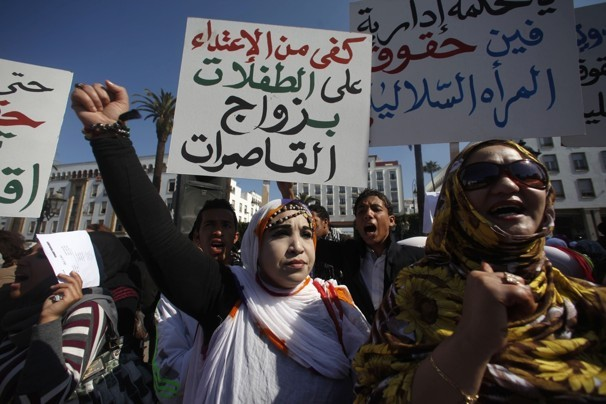 """File photo of Moroccans attending a women's rights rally while holding placards reading """"Stop abusing girls"""" in Rabat February 20, 2012."""