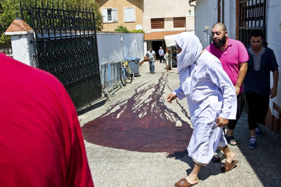 Islamic faithful walk past the blood-stained pavement outside the entrance of the Es Salam mosque following afternoon prayers in Montauban