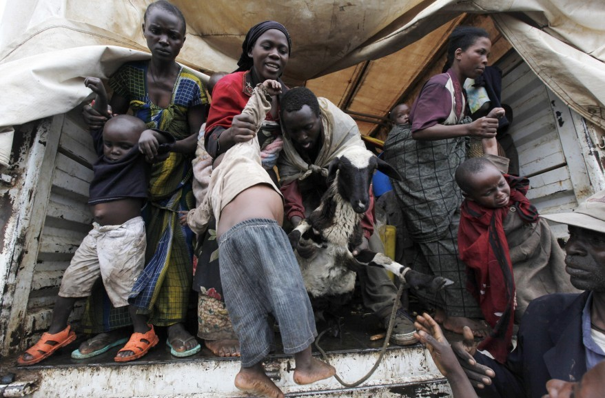 Refugees from Democratic Republic of Congo jump from a UNHCR at Nyakabande refugee transit camp in Kisoro town (Reuters)