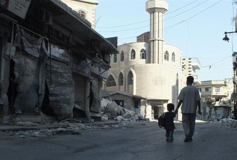 A man walks with his child at the Qusour area after Syrian President Bashar Assad forces shelled the neighbourhood in the central of Homs city August 5, 2012. REUTERS/Yazan Homsy