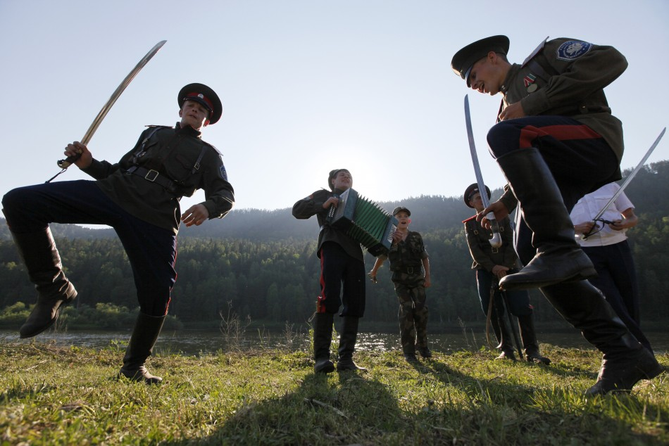Russian Cossacks perform traditional dance with sabres during annual Mansky tourist three-day-long festival near Mana river in Siberian Taiga, Reuters