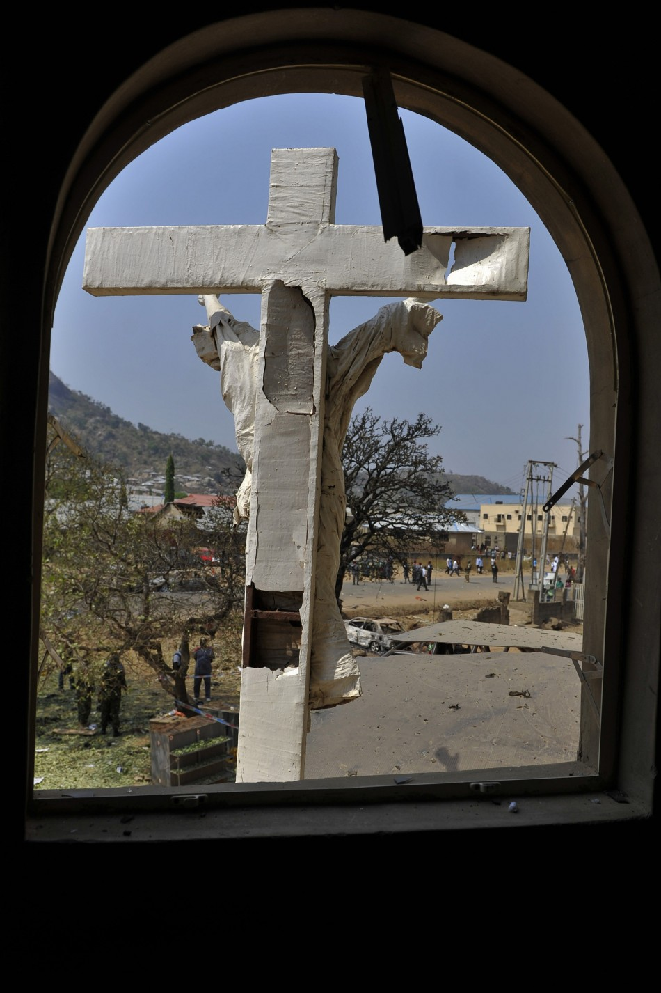 A damaged crucifix overlooks the scene of a bomb explosion at St. Theresa Catholic Church at Madalla