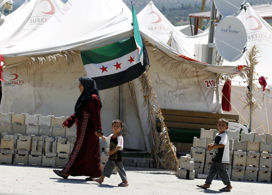 A Syrian refugee woman walks with children at the Boynuyogun refugee camp in Hatay province on the Turkish-Syrian border, Reuters