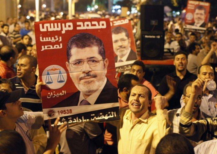 Supporters of Egypt's President Mohamed Mursi chant while carrying posters of him in front of the presidential palace in Cairo