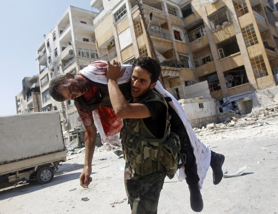 A Free Syrian Army fighter carries the body of a fellow fighter during clashes in Aleppo, Reuters