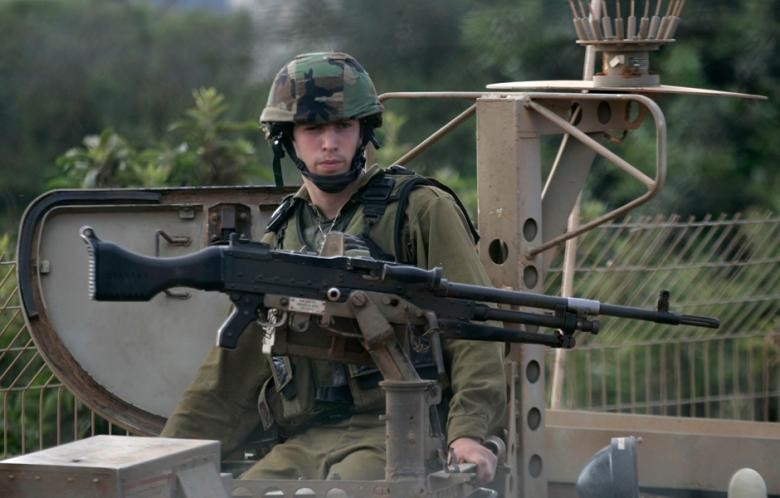 An Israeli soldier patrols near the Lebanese-Israeli border as seen from the southern Lebanese village of Kfar Kila, 5 June 2011. (Photo: Reuters - Karamallah Daher)