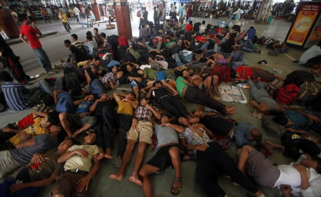 People from India's northeastern states rest while waiting for the train bound for the Assam state at a railway station in Kolkata