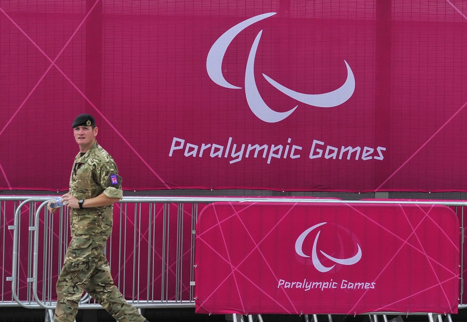 A member of the British army walks past a perimeter fence at the Olympic Park in Stratford