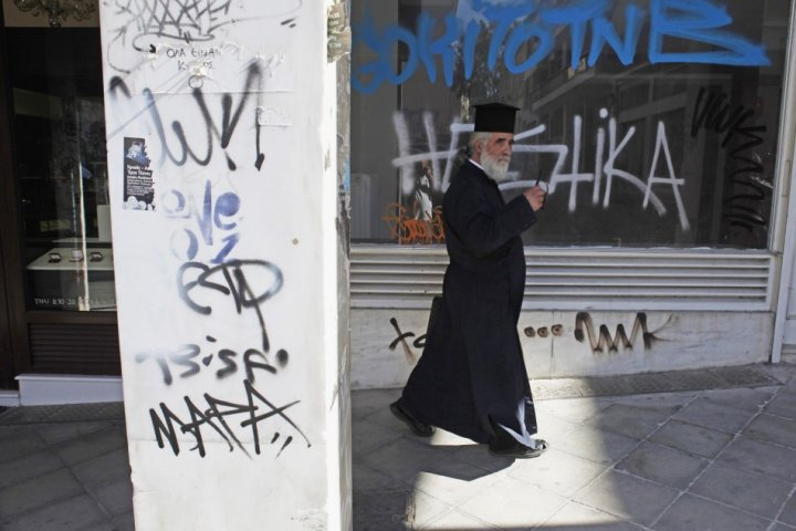 A Greek Orthodox priest walks past a closed shop in central Athens (Photo: REUTERS)