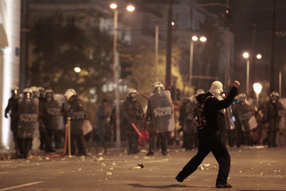 (Photo: A protester throws a stone at policemen during riots at central Syntagma square in Athens)