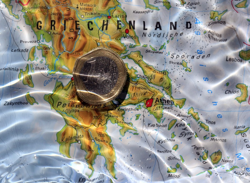 One Euro coin is displayed in water over map showing Greece in this picture illustration taken in Munich