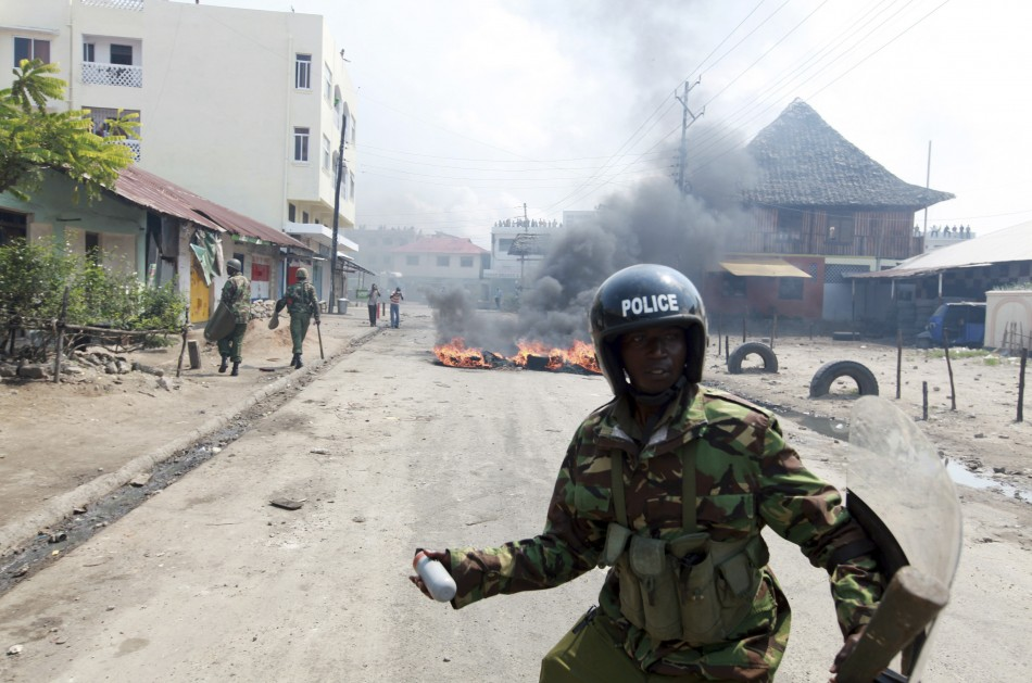 A policeman prepares to lobe a tear-gas canister in the direction of protesting youths in the coastal town of Mombasa