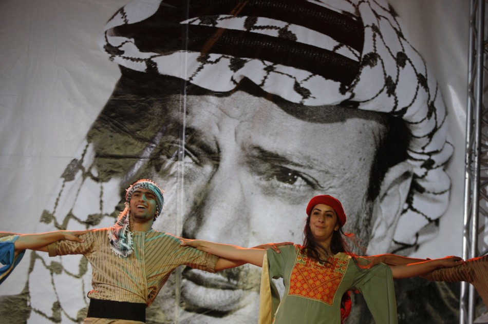 Palestinian dancers perform in front of a banner depicting late Palestinian leader Yasser Arafat