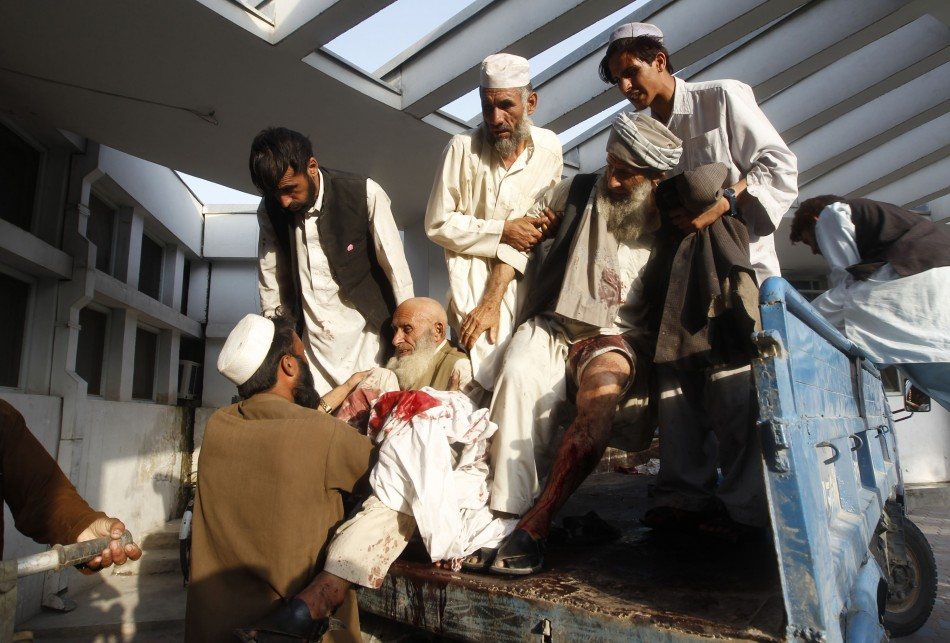 Afghan men assist those injured in a bomb blast as they arrive at a hospital in Jalalabad