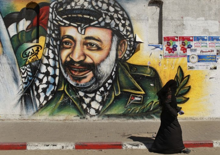 Palestinian woman walks past a mural depicting late leader Arafat in Gaza