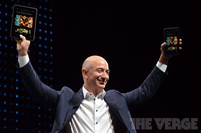 Amazon CEO Jeff Bezos holding up the two versions of the Kindle Fire HD