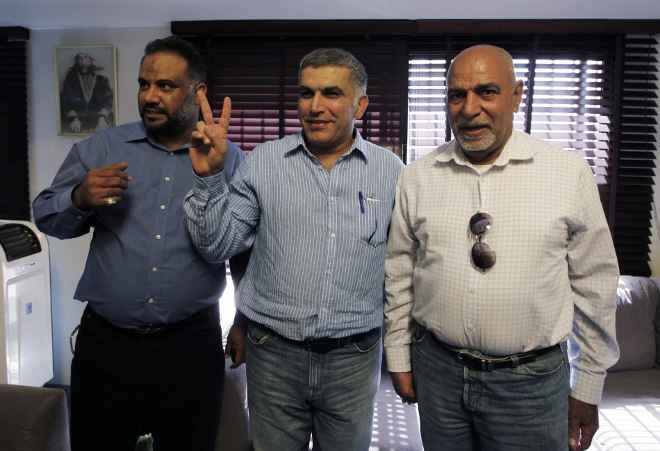 Bahrain human rights activist Nabeel Rajab flashes a victory sign as he poses for photographers with his family members