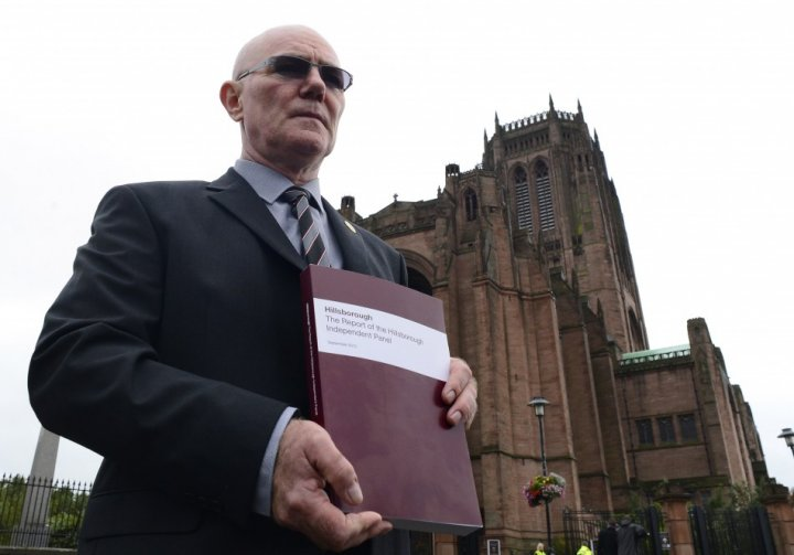 Steve Kelly of the Hillsborough Justice Campaign poses for members of the media with a copy of the independent report into the 1989 Hillsborough Disaster (Reuters)