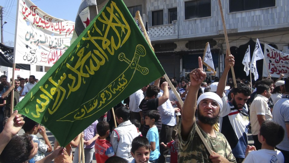A member of the Free Syrian Army holds a flag during a protest against Syria's President Bashar al-Assad