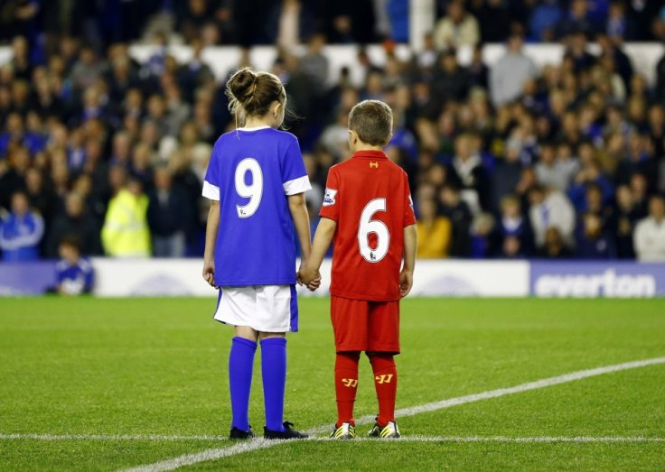 Children wearing Everton and Liverpool shirts pay their respects to the 96 victims of the Hillsborough disaster (Reuters)