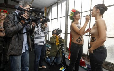 Activists from the topless womens rights group Femen prepare for the inauguration of the training camp in Paris